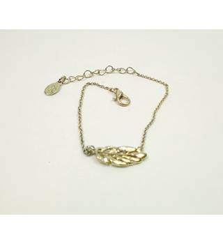 Accessorize gold tone chain with feather bracelet