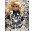 Porcelain doll with blonde hair and wearing blue dress