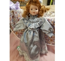 Porcelain doll wearing a silver dress and bow