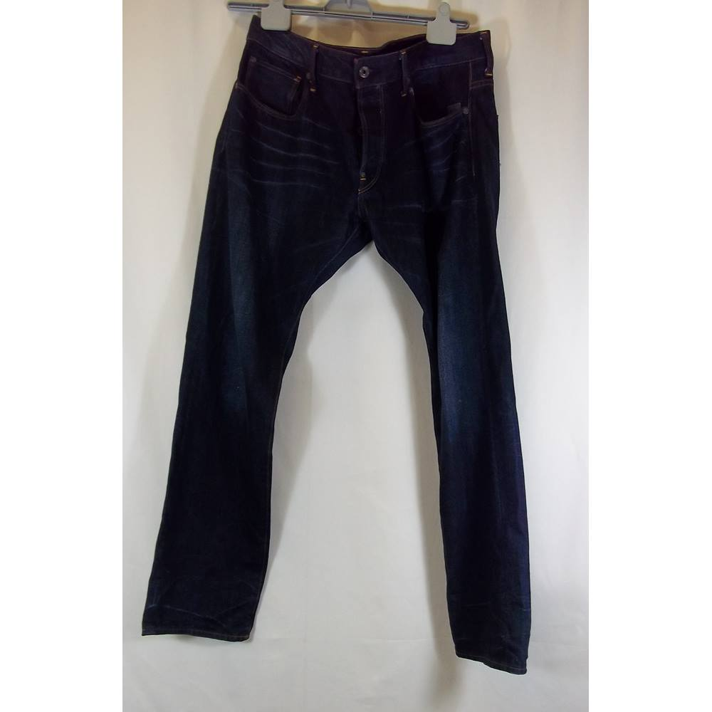fd7e326f135 Oxfam Shop London Brand: G Raw Star Attac Jeans The Attacc jeans features  rugged back pockets, one with a half-concealed zip, and both with  flat-rivets and ...