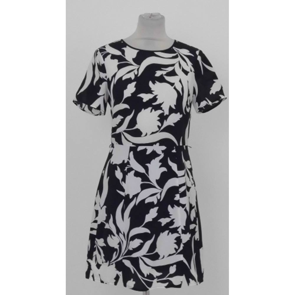 b08f8a033362 This floral monochrome print dress has a lined skirt and closes at the back  with an obvious zip. It has a scoop neckline and short sleeves.